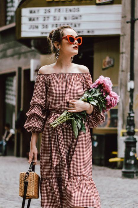 Looks de primavera; chica con vestido estilo campesino de cuadros rojos y blancos, con lentes de marco grueso y rojo, con bolsa de mano de mimbre, sosteniendo un ramo de flores rosas