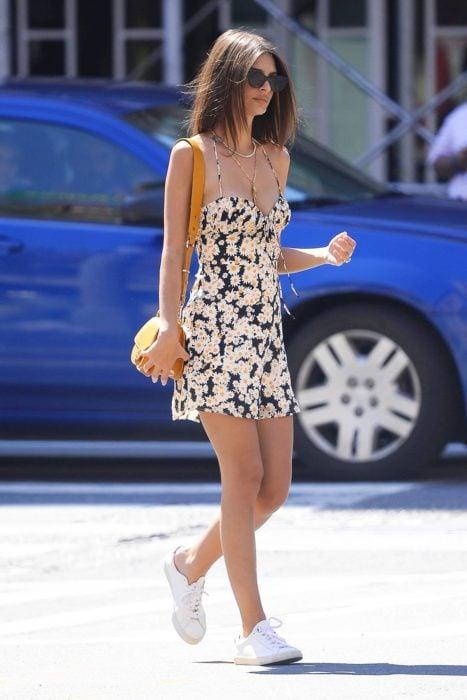 Looks de primavera; Emily Ratajkowski caminando en la calle con vestido negro con estampado de flores margaritas, con tenis blancos y una bolsa amarilla