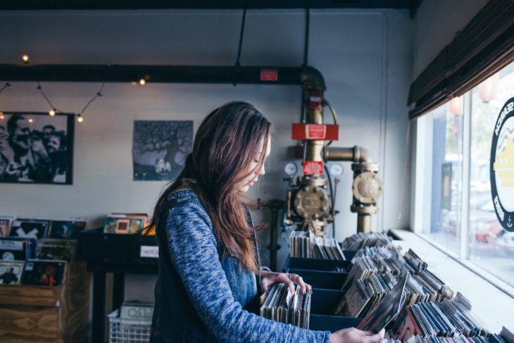 una mujer elige un disco de vinilo de un estante se ve de perfil