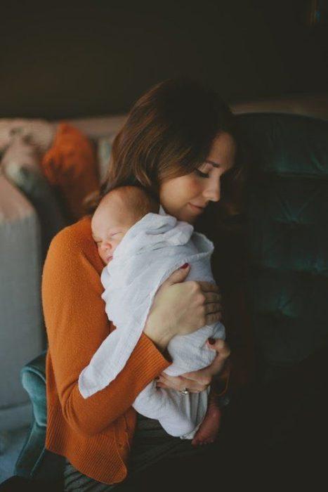Mamá joven cargando a su bebé de meses