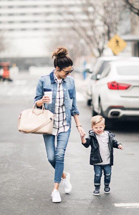 Mamá joven sosteniendo un café agarrando a su hijo de la mano