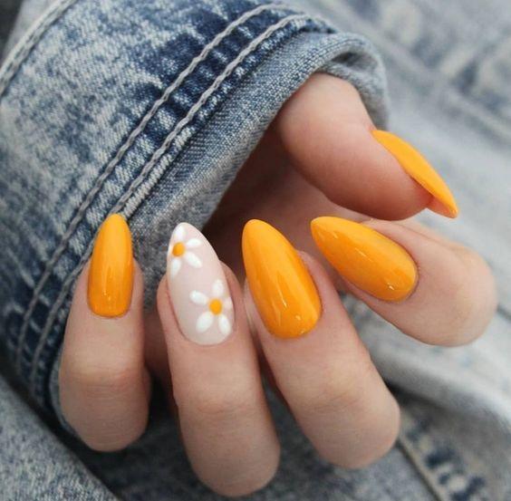 Mano de mujer con uñas en tono amarillo con margaritas y en estilo almendra