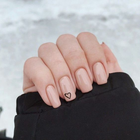 Mano de una chica con uñas cuadradas y en tono rosa pastel