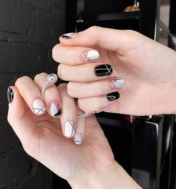 Manos de mujer con uñas redondeadas y pintandas en colores oscuros y grises