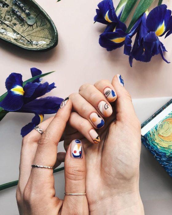 Manos de mujer sobre una mesa decorada con flores y con la uñas pintadas en figuras de colores