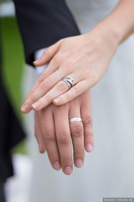 Manos una sobre otra, mostrando los anillos de compromiso