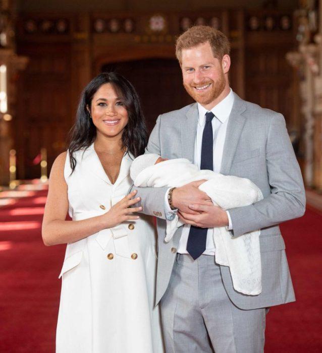 Meghan Markle y el príncipe Harry caminando sobre una alfombra roja y cargando a su primogénito en brazos