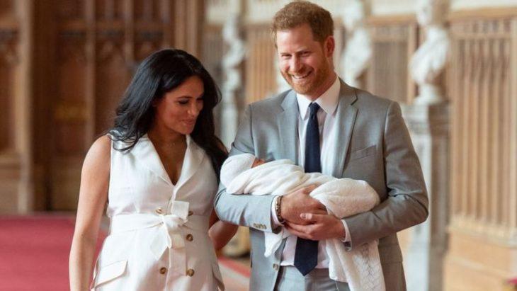 Meghan Markle y el príncipe Harry abrazados de manera lateral, sosteniendo a su bebé en brazos