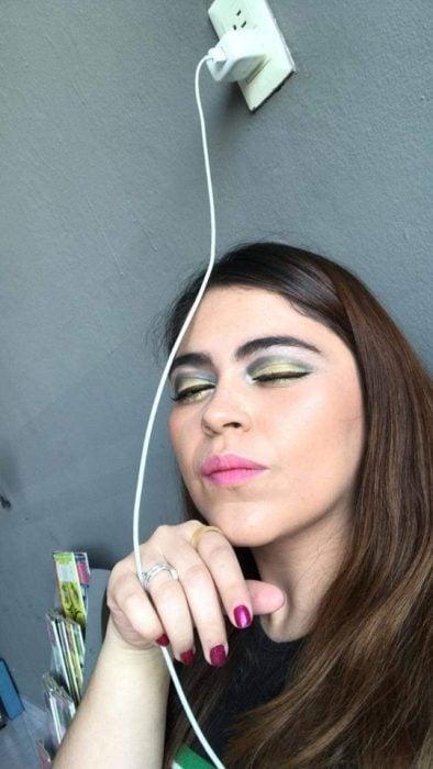 Chica ayuda a su mejor amiga a maquillarse vía Whatsapp, selfie de mujer con maquillaje mal hecho, sombras amarilla y negra, labial rosa y uñas magenta