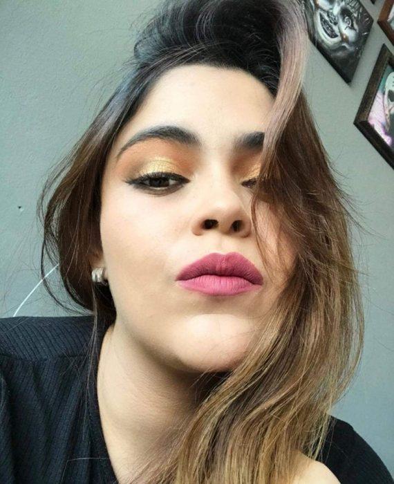 Chica ayuda a su mejor amiga a maquillarse vía Whatsapp; selfie de mujer con maquillaje de día, sombras anaranjada y amarilla, labial rosa