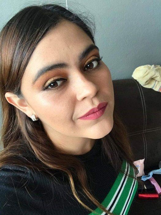 Chica ayuda a su mejor amiga a maquillarse vía Whatsapp; selfie de joven con maquillaje bonito de día, sombras anaranjada y amarilla, delineado cat eye y labial rosa