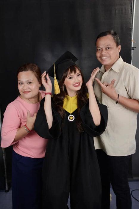Patricia Banzuela, chica con alopecia el día de su graduación parada junto a sus padres en la foto del recuerdo