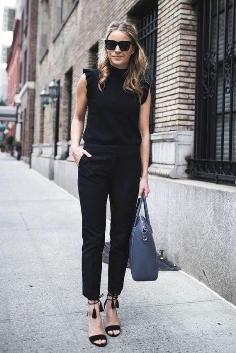 Mujer joven vestida de negro con bolsa azul caminando por la calle