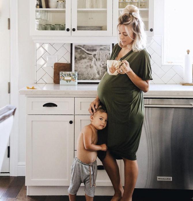 Mujer con una taza en la mano y un niño abrazando la panza de su mamá