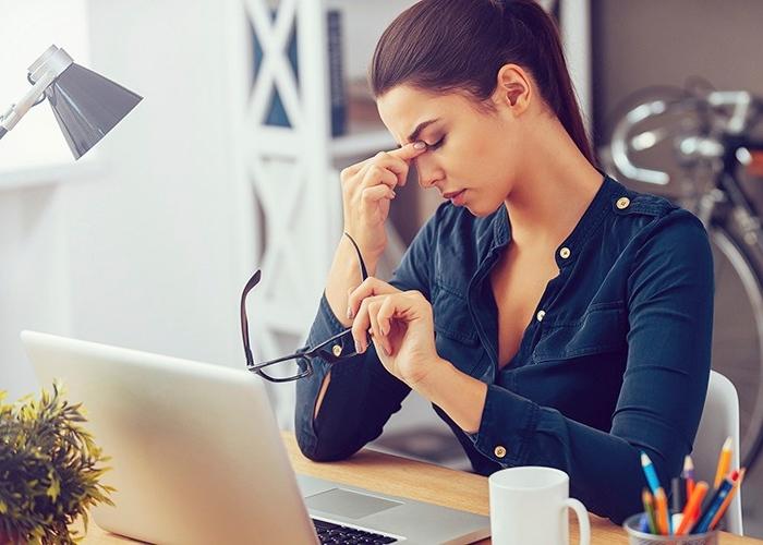 Mujer estresada en la oficina agarrándose la frente