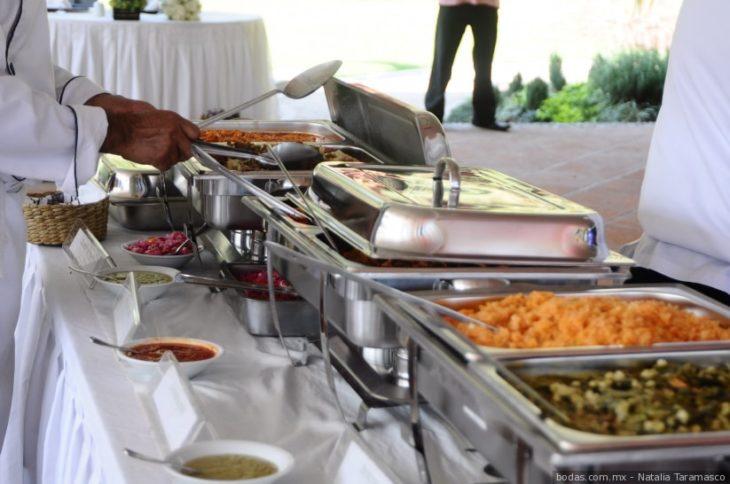 Barra de un buffet mostrando los platillos mientras una persona los toma con una cuchara