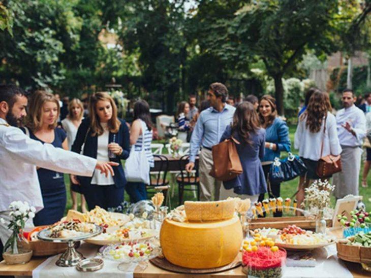 Personas caminando en una boda mientras ven qué comida elegir del buffet