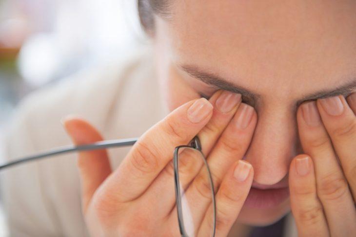 Mujer joven con los dedos sobre los ojos cerrados