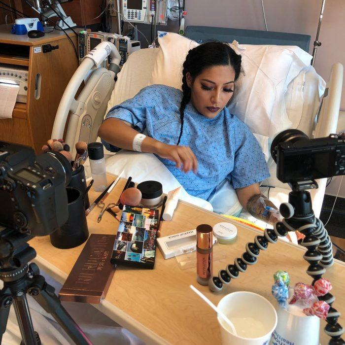 Blogger de belleza Alexis Jayda recostada en una cama de hospital con cámaras grabando un tutorial de belleza antes de dar a luz a su bebé