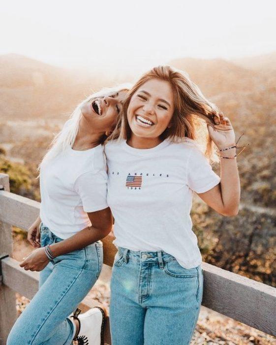 Mujeres recargadas entre sí riendo