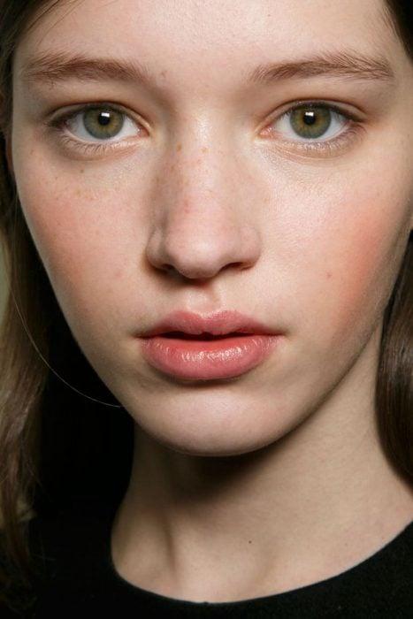 Primer plano de mujer blanca sin maquillaje mejillas rosadas