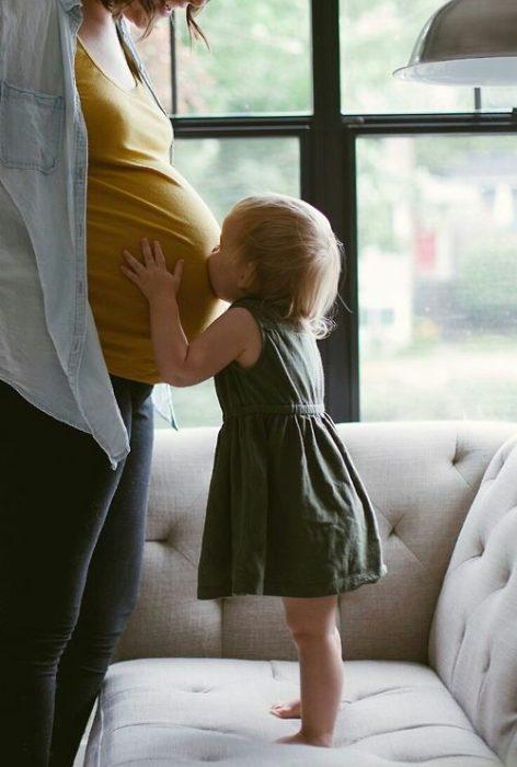Bebé besando a su mamá embarazada en la panza
