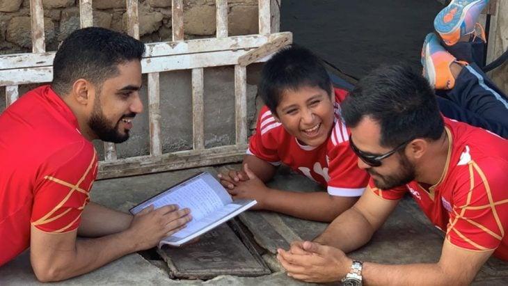 Empresario árabe, Yaqoob Yusuf Ahmed Mubarak jugando en el suelo con Victor Martín Angulo Córdoba, niño peruano que hace la tarea bajo un poste de luz