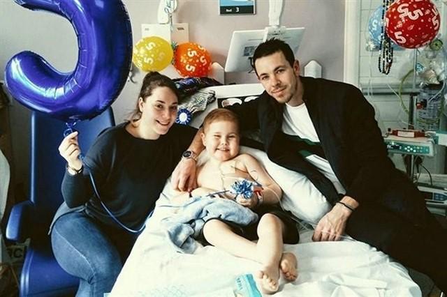 Oscar Saxelby-Lee, niño con cáncer, sentado en una cama de hospital junto a sus padres, todos sonriendo para una fotografía mientras sostienen globos de helio