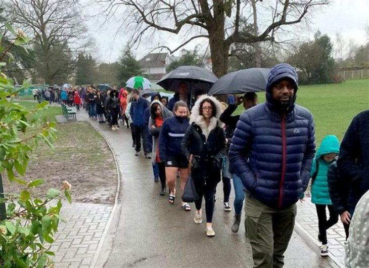 Personas haciendo fila afuera de una escuela para registrarse como donantes de médula ósea para Oscar Saxelby-Lee