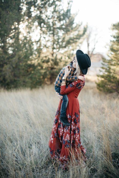 Cosas graciosas que dicen los niños; mujer rubia, vestido rojo y largo de flores, con sombrero negro; mamá cargando a su hijo en el campo