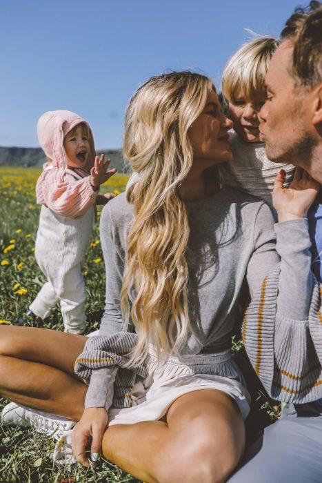 Cosas graciosas que dicen los niños; familia sentada en el campo con flores; mujer rubia de cabello largo y ondulado; mamá, papá y dos hijos