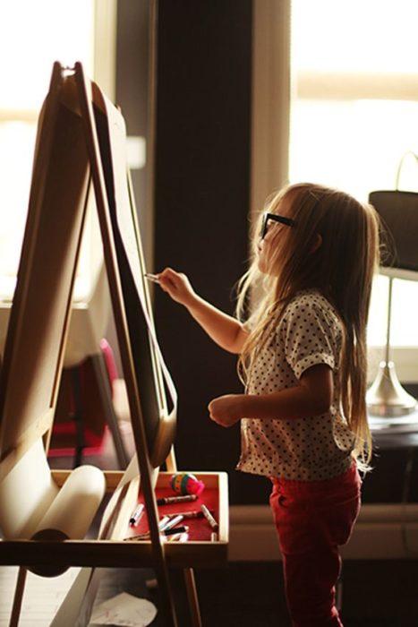 Cosas graciosas que dicen los niños; niña con lentes pintando en un bastidor