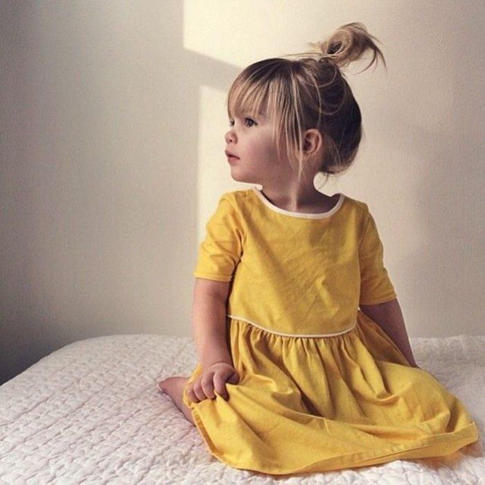 Cosas graciosas que dicen los niños; nila rubia con vestido amarillo sentada