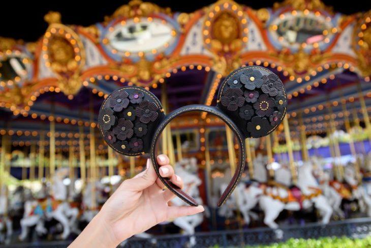Chica sosteniendo unas orejas de Mickey Mouse diseñadas por Coach
