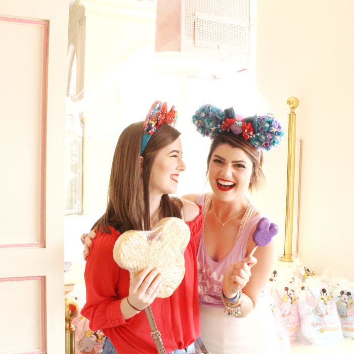 Chicas en un parque de Disney posando con sus ojeras de Mickey Mouse hechas con flores