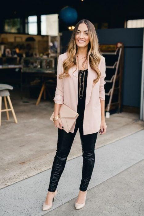 Chica usando unos leggings de cuero con un conjunto de color rosa al igual que los zapatos y la cartera