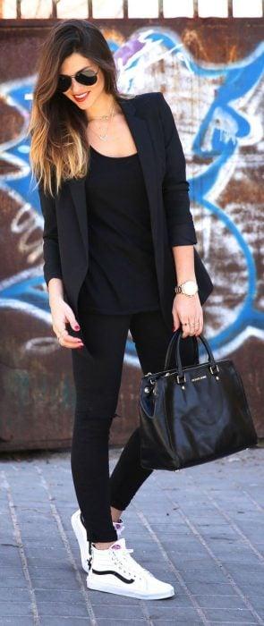 Chica usando un atuendo negro con tenis de color blanco marca Vans