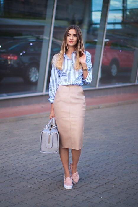 Chica parada en la calle usando un traje de falda de lápiz color rosa, blusa de líneas en color azul y zapatos color rosa