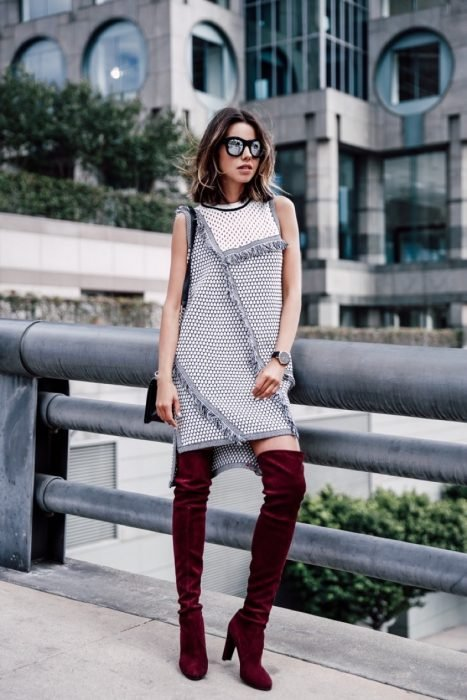 Chica parada sobre una calle posando para una foto mientras usa un vestido de color gris con estampado y botas largas de color guinda