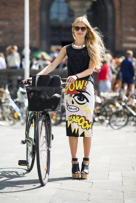 Chica parada junto a su bicicleta posando para una fotografía mientras usa una falda de estampado pop art, blusa negra y zapatos negros