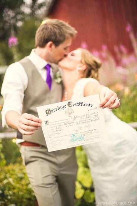 Una pareja de casados mostrando su acta de matrimonio
