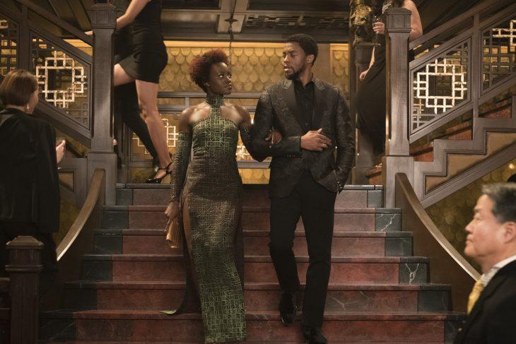 T'Challa y Nakia tomados de las manos, bajando las escaleras juntos, escena película Black Panther, Chadwick Boseman, Lupita Nyong'o