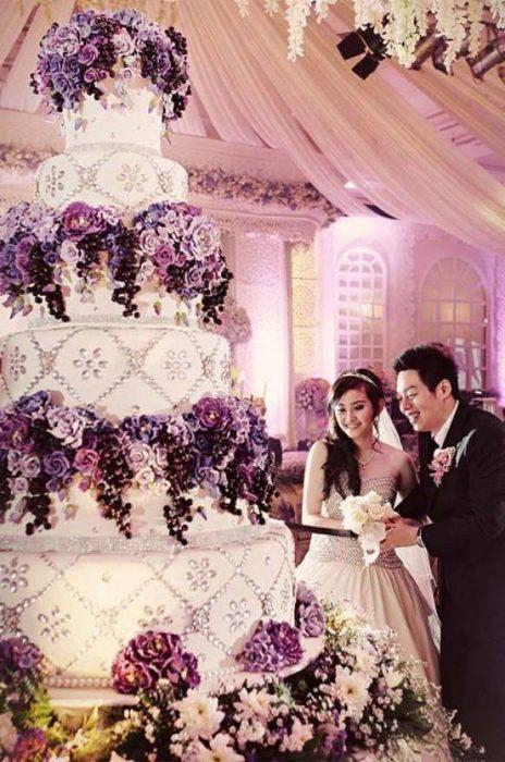 Pareja de novios sosteniendo una espada en las manos mientras cortan una rebanada de su enorme pastel de bodas decorado con flores moradas