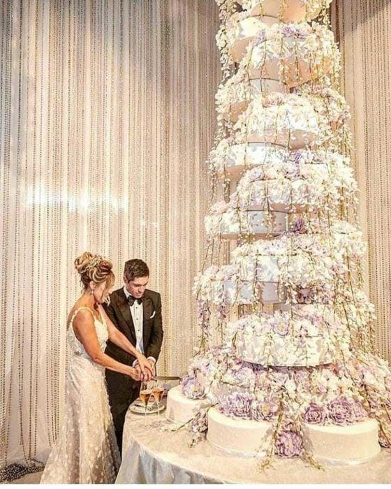 Pareja de novios el día de su boda parados frente a un enorme pastel decorado con flores moradas
