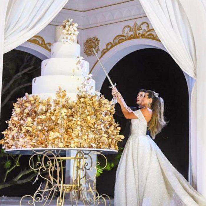 Pareja de novios sosteniendo una espada para cortar su enorme pastel de bodas
