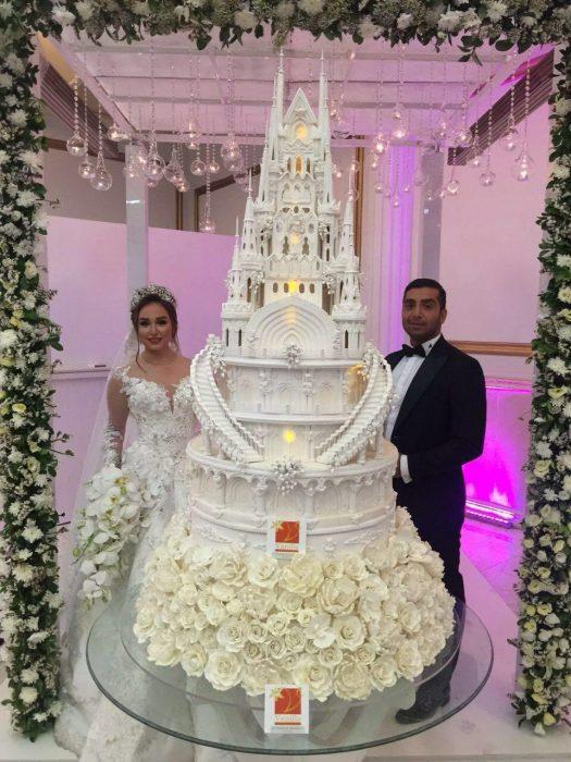 Pareja de novios el día de su boda parado a un lado de su enorme pastel de bodas con diseño de un castillo