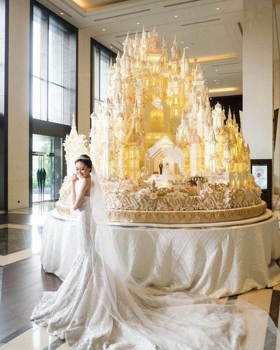 Novia el día de su boda parada frente a un enorme pastel de bodas en forma de castillo