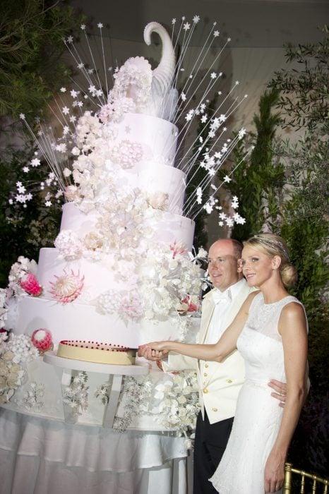 Pareja de novios abrazados mientras cortan una de las tortas de su pastel de bodas