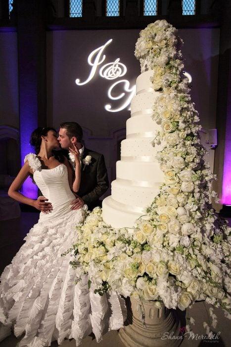 Pareja de novios parados frente a su enorme pastel de bodas decorado con flores rosas mientras se dan un beso