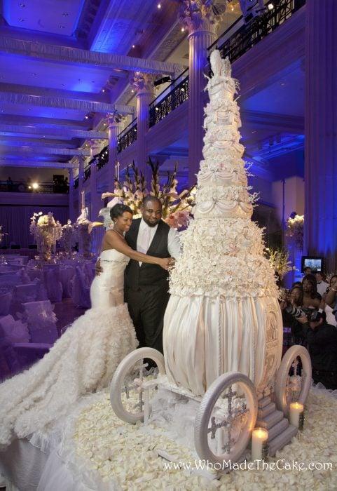 Pareja de novios parados frente a un pastel de bodas de varios pisos para cortar su primera rebanada en un pastel montado en una carroza